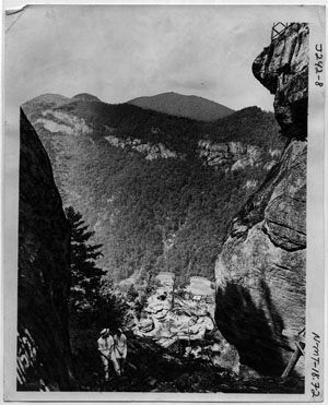 """Awe Inspiring Scenery, Showing Rugged Rock Formation at Chimney Rock."" Photograph believe to be made by George Masa, not dated.  Published by the Asheville Postcard Company.  From the North Carolina Collection at Pack Library, Asheville, N.C.  Used by permission."