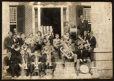 Photograph of B. J. Pfohl and the Salem Band in front of Main Hall at Salem College [date unknown]. B J. Pfohl is standing in the right rear of the image. From the collections of Forsyth County Public Library, Digital Forsyth, Winston-Salem, North Carolina.  Used by permission from the Forsyth County Public Library.
