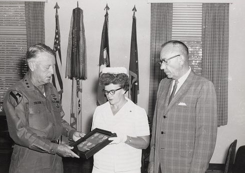 """LTG John J. Tolson, Commanding General XVIII Corps, presents the Silver Star and Bronze Medal posthumously to Glanor Gay Best and Hugh Best Jr., who are receiving the medals on behalf of their deceased son, Hugh E. Best III, who was killed in action in 1969 in the Vietnam War,"" by C. Gene Tyree DAC at Fort Bragg, North Carolina, published in 1969. Image is presented on East Carolina University's Digital Collection."