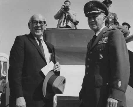 General Frank A. Armstrong, Jr. and an unidentified man standing together during Eisenhower's visit to Elmendorf Air Force Base in Anchorage, Alaska. Photographer and other military officers behind them.