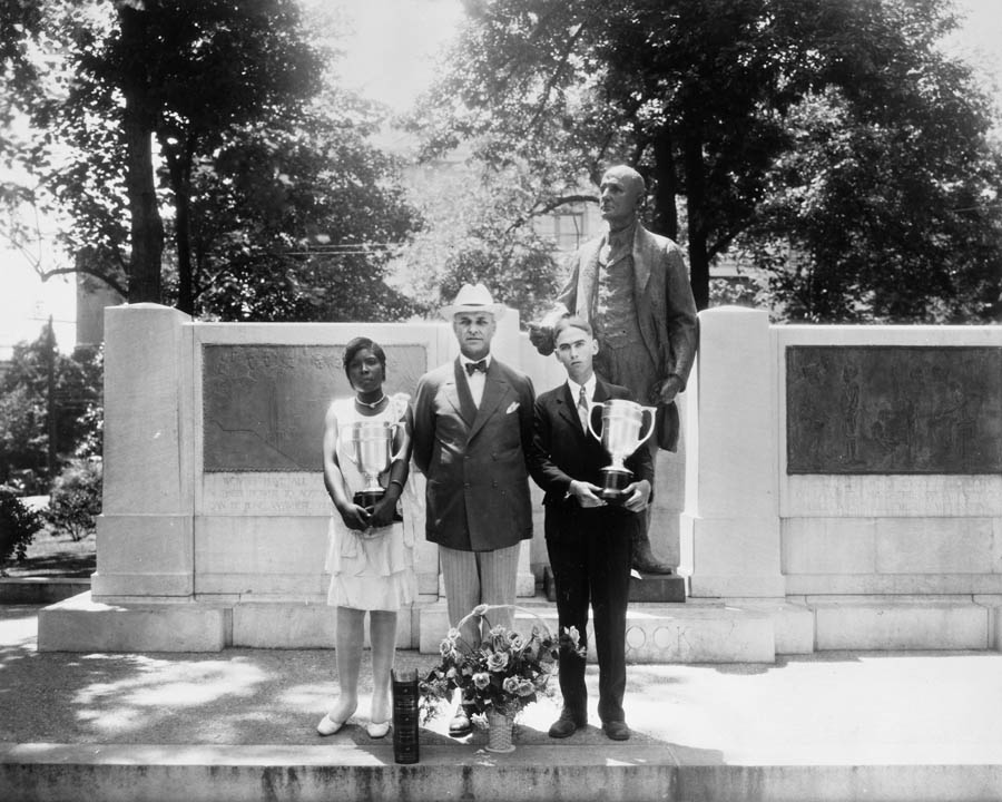 Winners of the high school Live-at-Home essay contest, Ophelia Holley and Leroy Sossamon, pose with Governor O. Max Gardner, June 23, 1930.